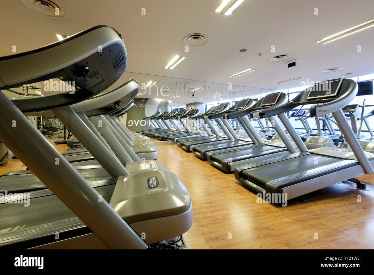 Rows of vacant treadmills at an empty gym - Stock Image