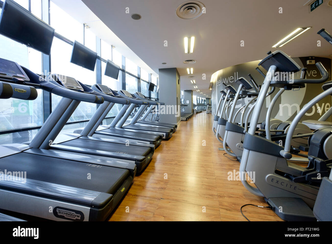 Rows of treadmills and other exercise machines at an empty gym - Stock Image