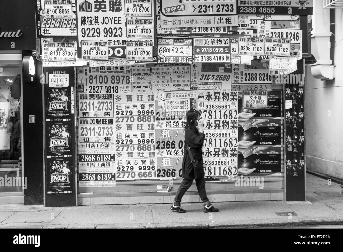 Renting Estate agent kiosk advertising telephone numbers in Hong Kong in Black and White - Stock Image