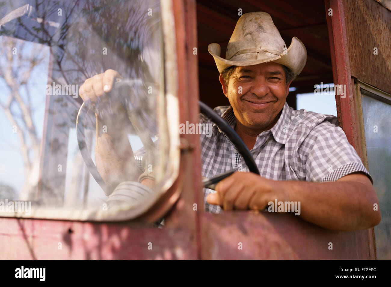 Farming and cultivations in Latin America. Portrait of middle aged hispanic farmer sitting proud in his tractor - Stock Image