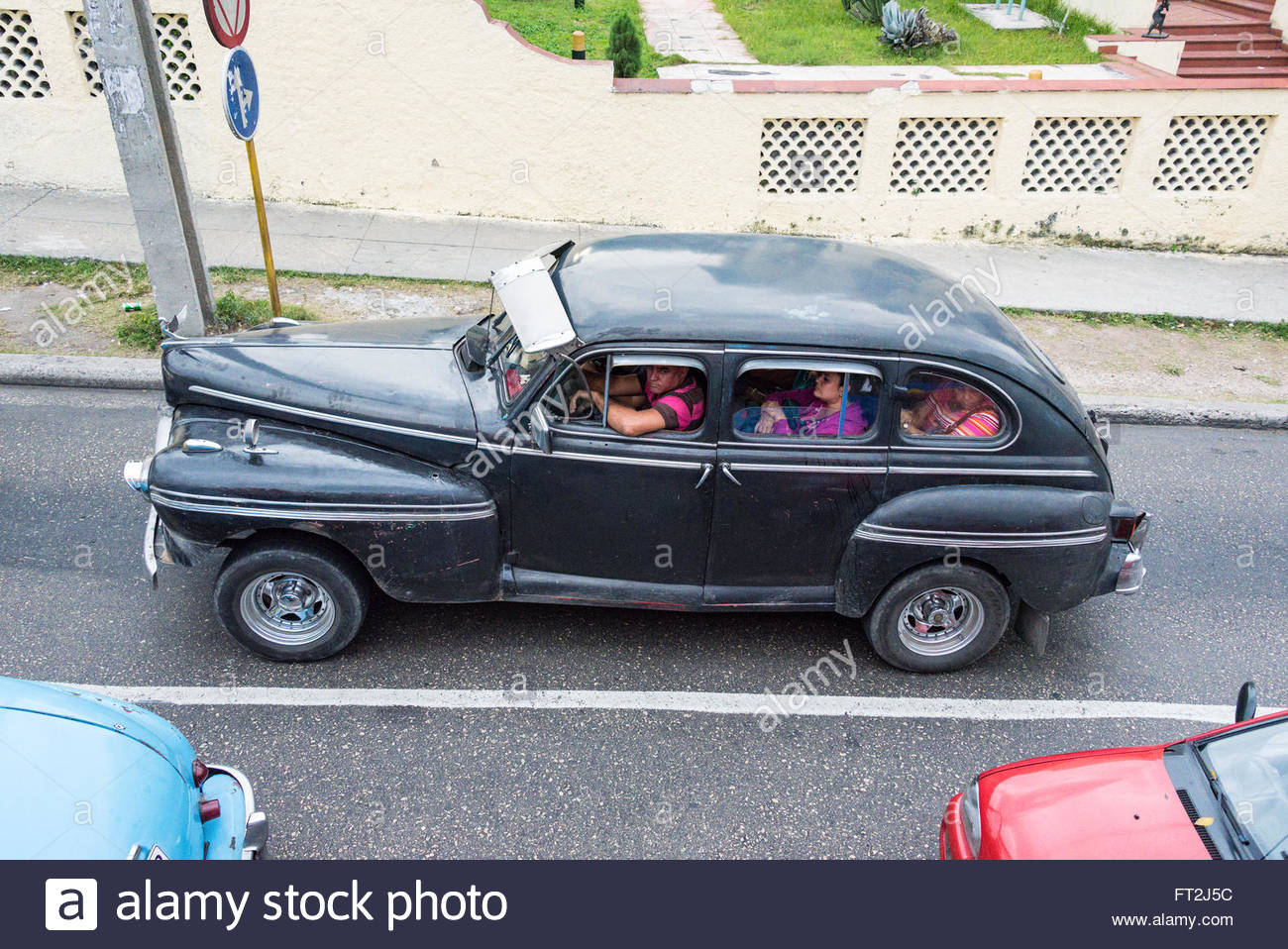 Vintage Ameican taxi cab carrying tourists on the back seat - Stock Image