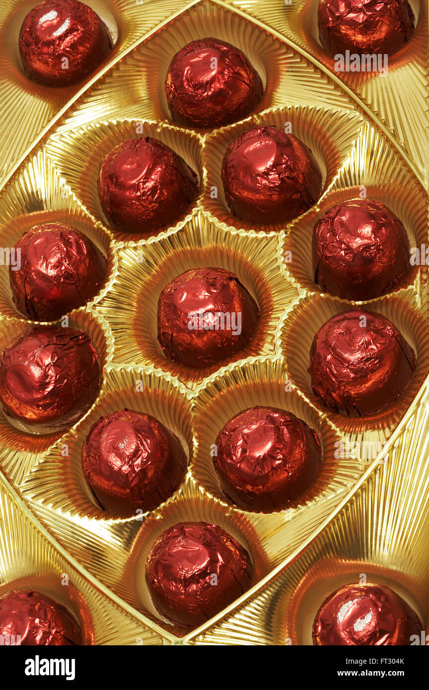 Chocolates In A Red Foil In A Beautiful Gold Box Stock Photo