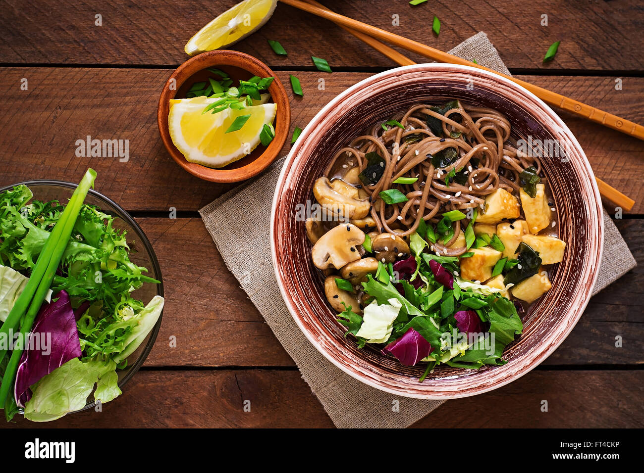 Miso and soba noodle soup with roasted tofu and mushrooms. Top view - Stock Image