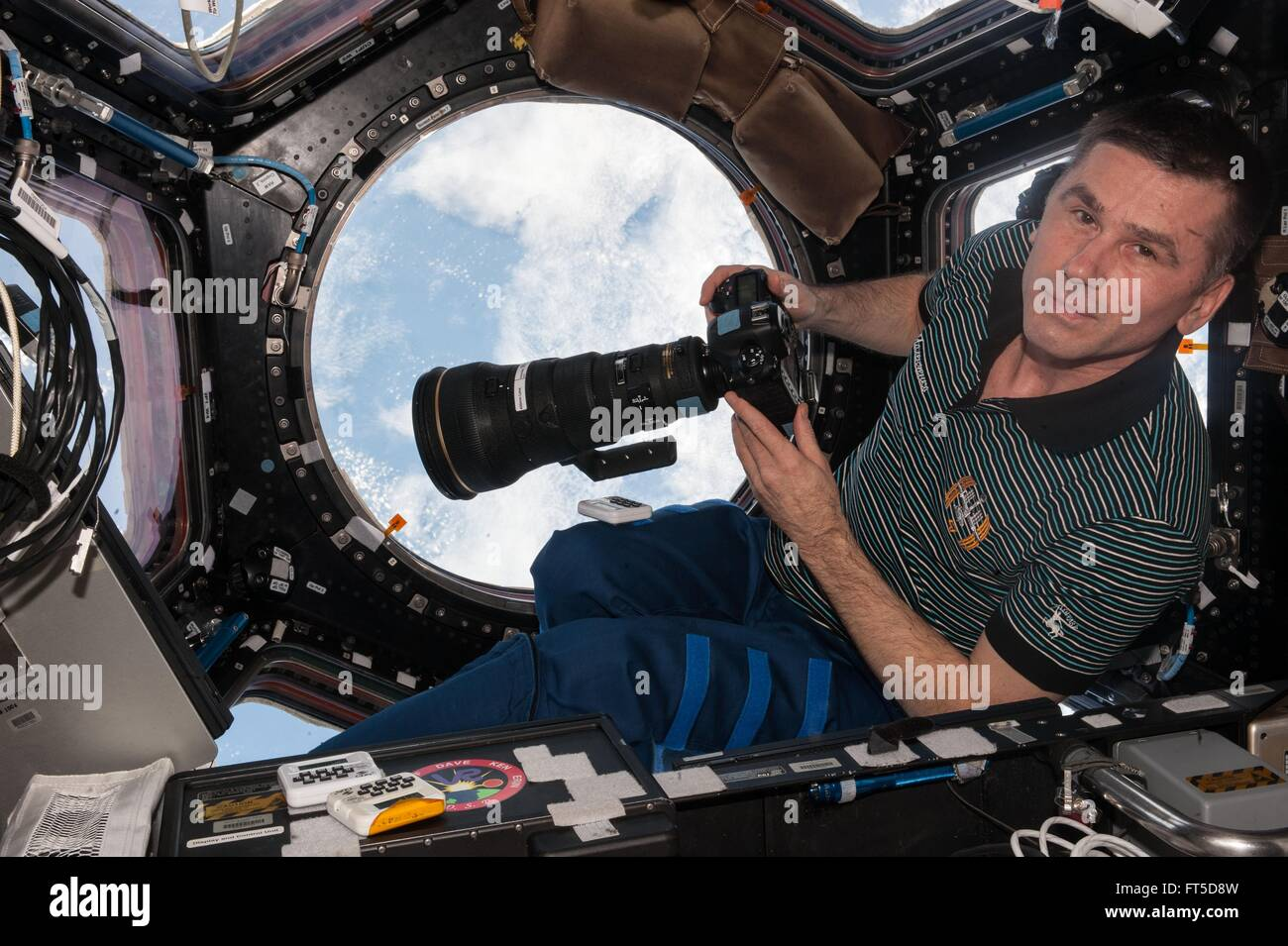 Russian cosmonaut Yuri Malenchenko inside the Cupola module preparing to take Earth pictures using a 400 mm lens - Stock Image