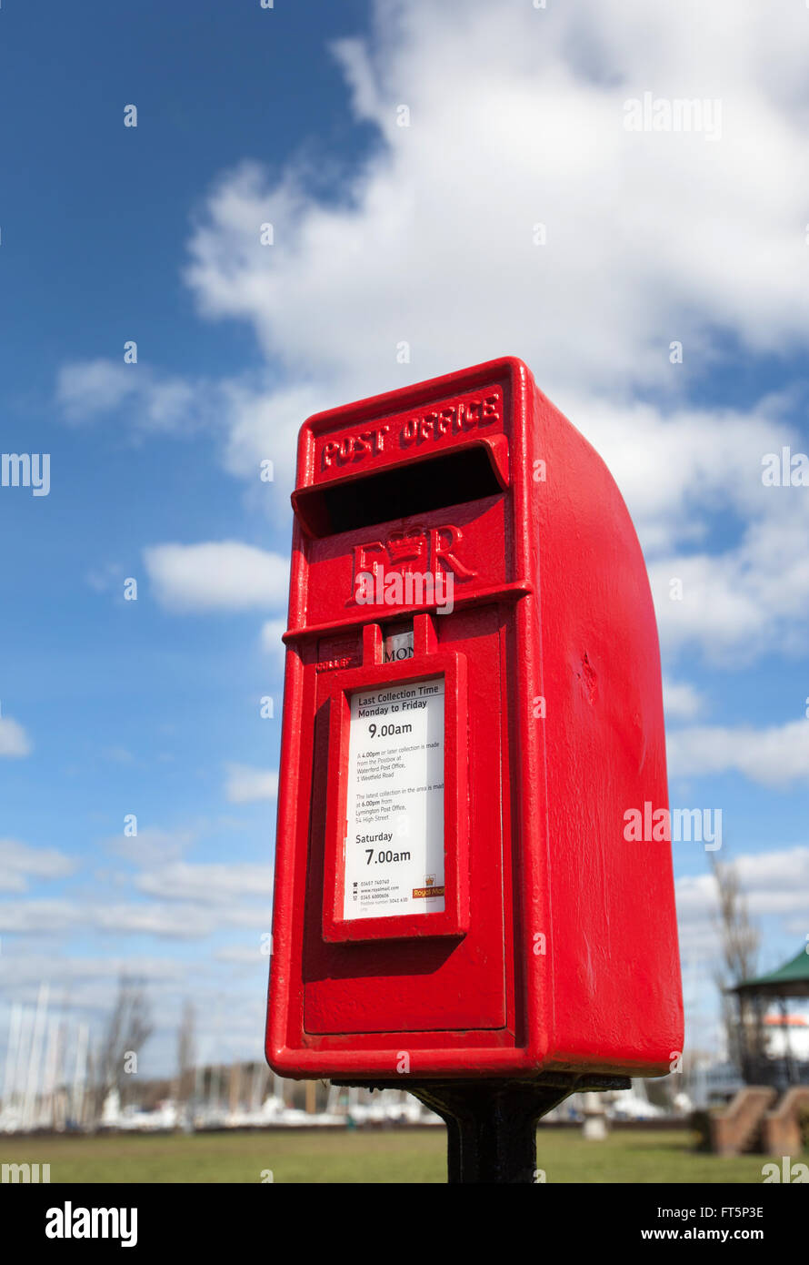 A red postbox pictured against a blue cloudy sky - Stock Image