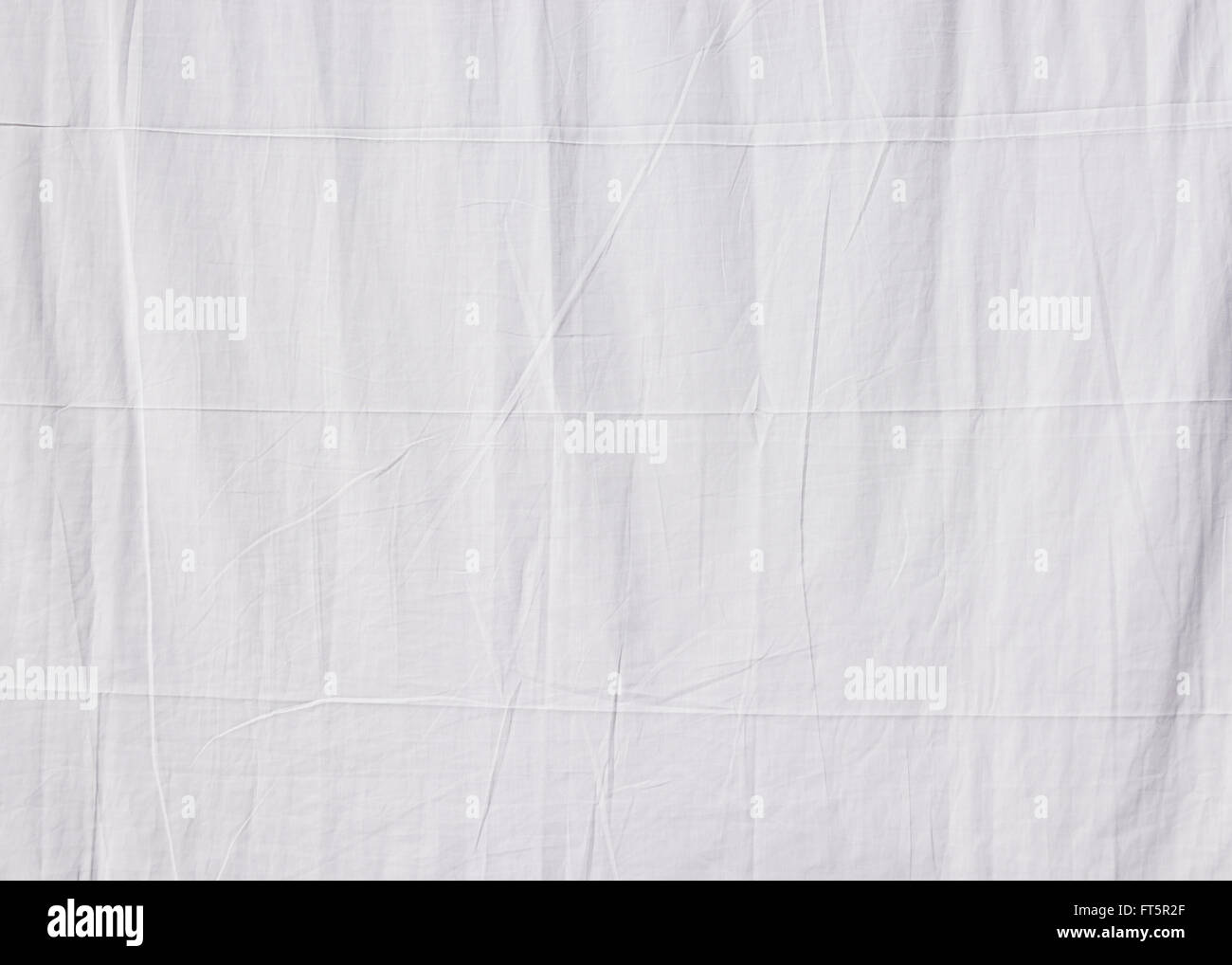 Closeup of a white cotton sheet drying in the sun - Stock Image