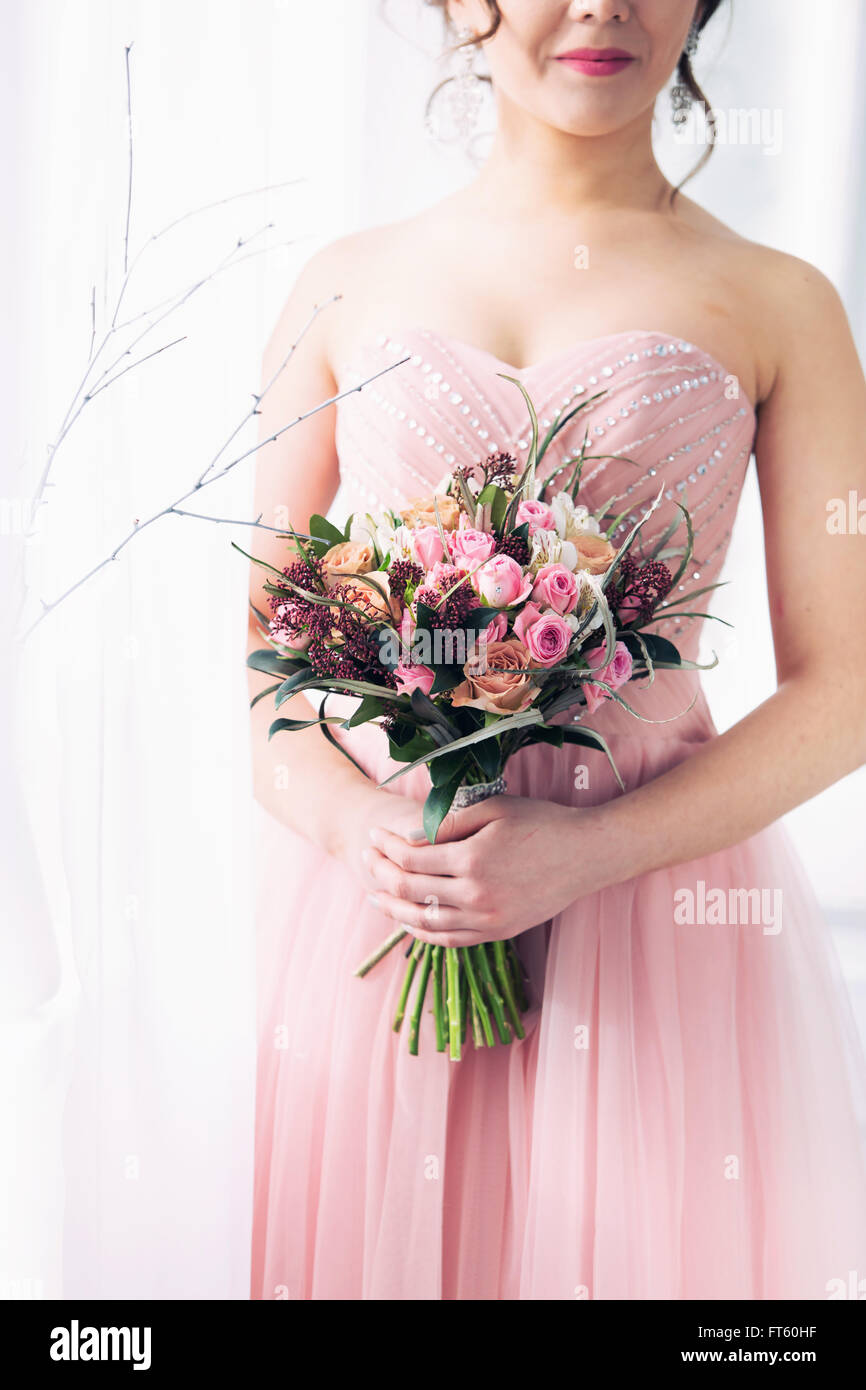 The Bride In A Pink Wedding Dress Holds In Hand A Bouquet From