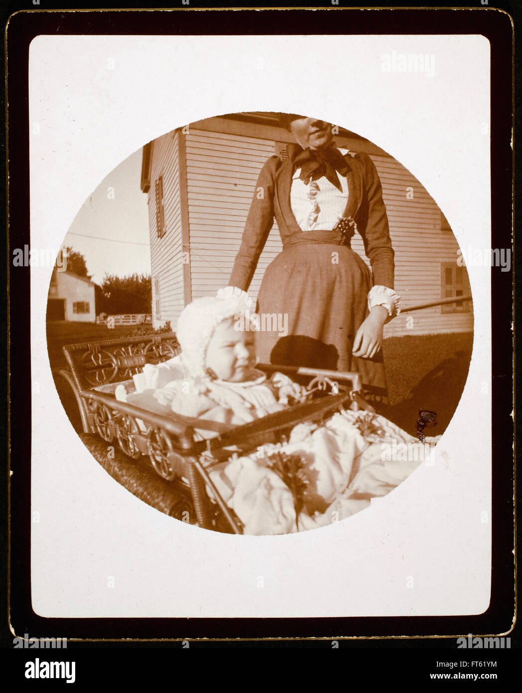 Unidentified Photographer - Baby in carriage, woman standing behind - Stock Image