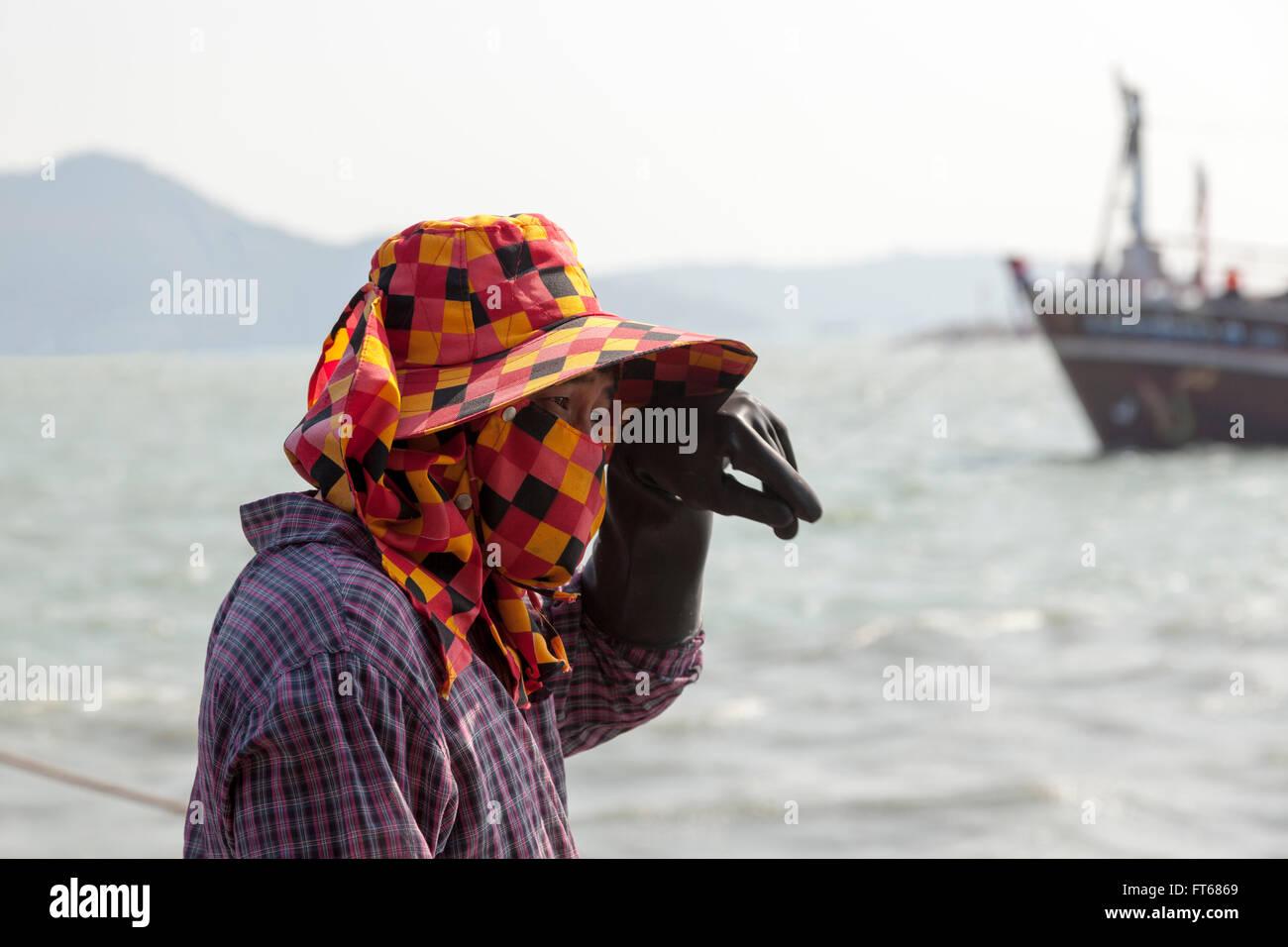 A fisherman protecting his head from the intense sun reflection (Ao Khlong Wan - Prachuap Khiri Khan province - - Stock Image