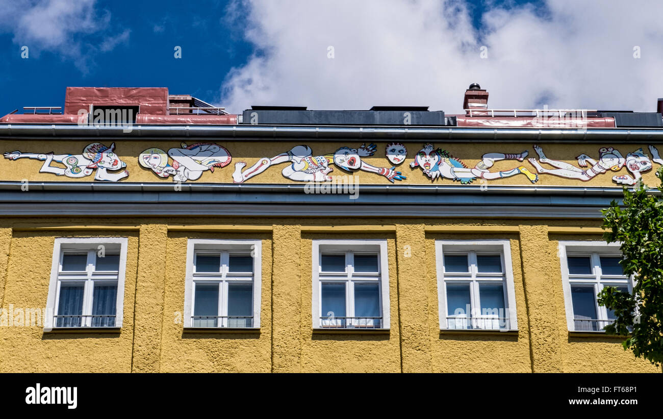 Berlin Apartment building, comical decorative frieze and yellow paintwork - Stock Image