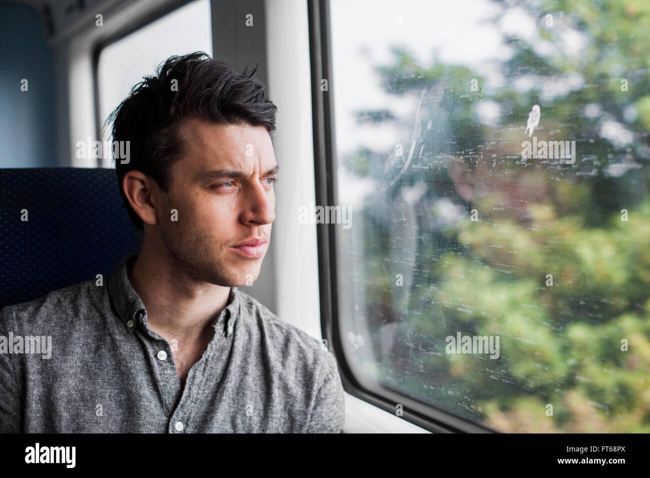 Thoughtful businessman looking through train window - Stock Image