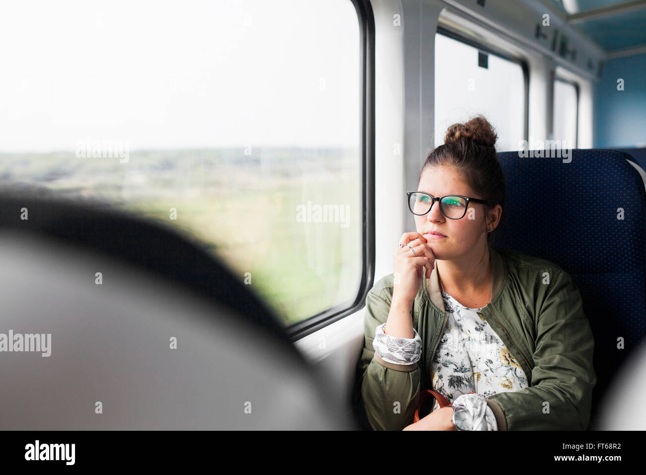 Thoughtful businesswoman with hand on chin looking through train window - Stock Image
