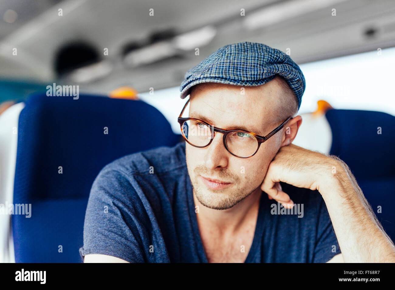 Thoughtful businessman travelling in train - Stock Image
