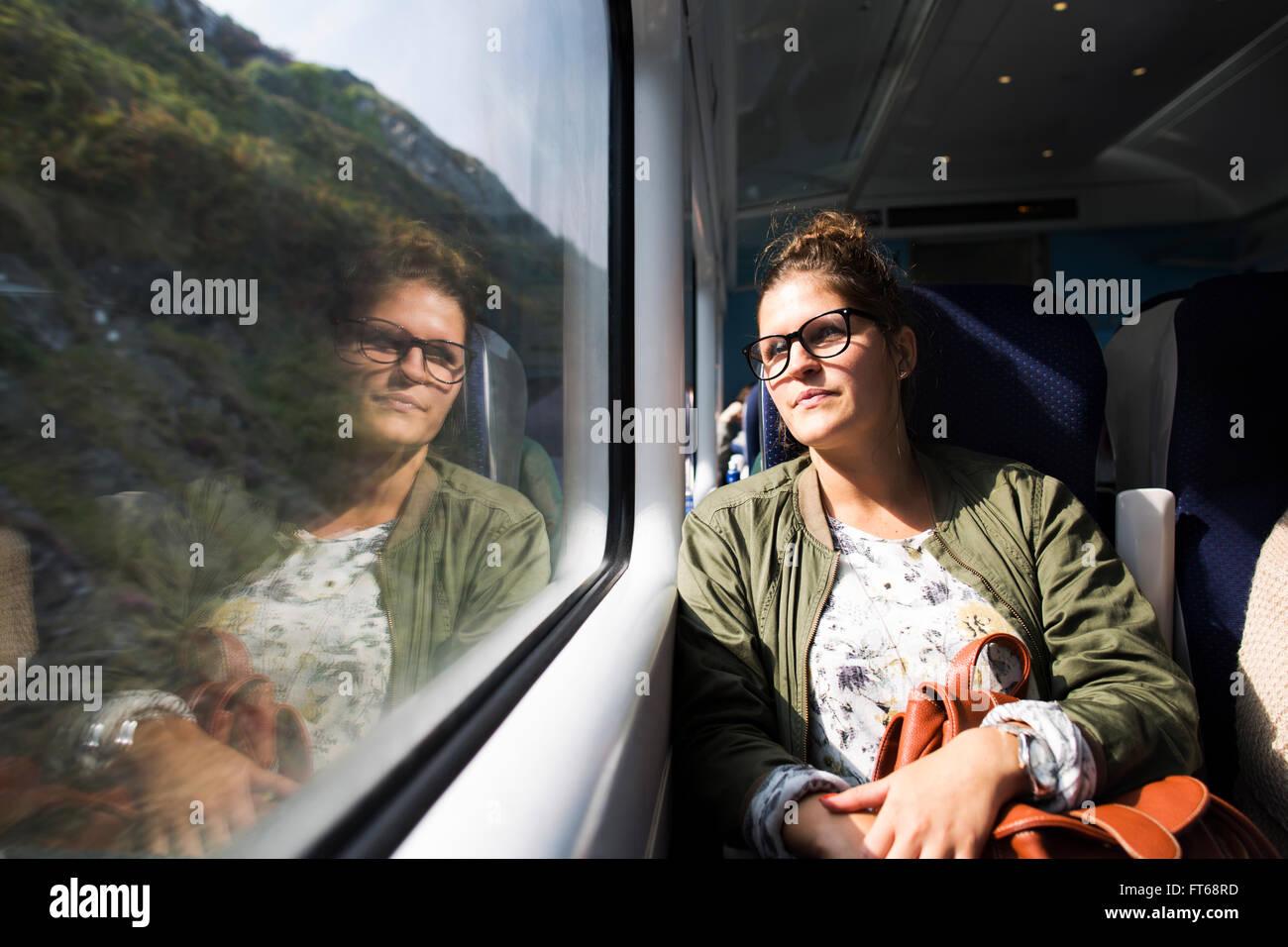 Thoughtful businesswoman looking through train window - Stock Image