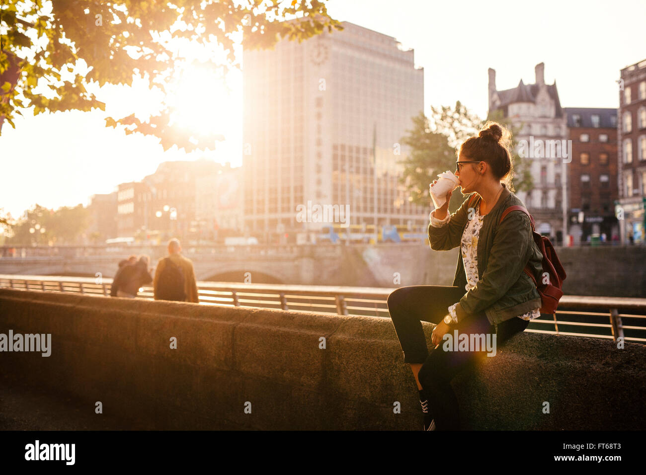 Woman drinking coffee while sitting retailing wall of bridge in city - Stock Image