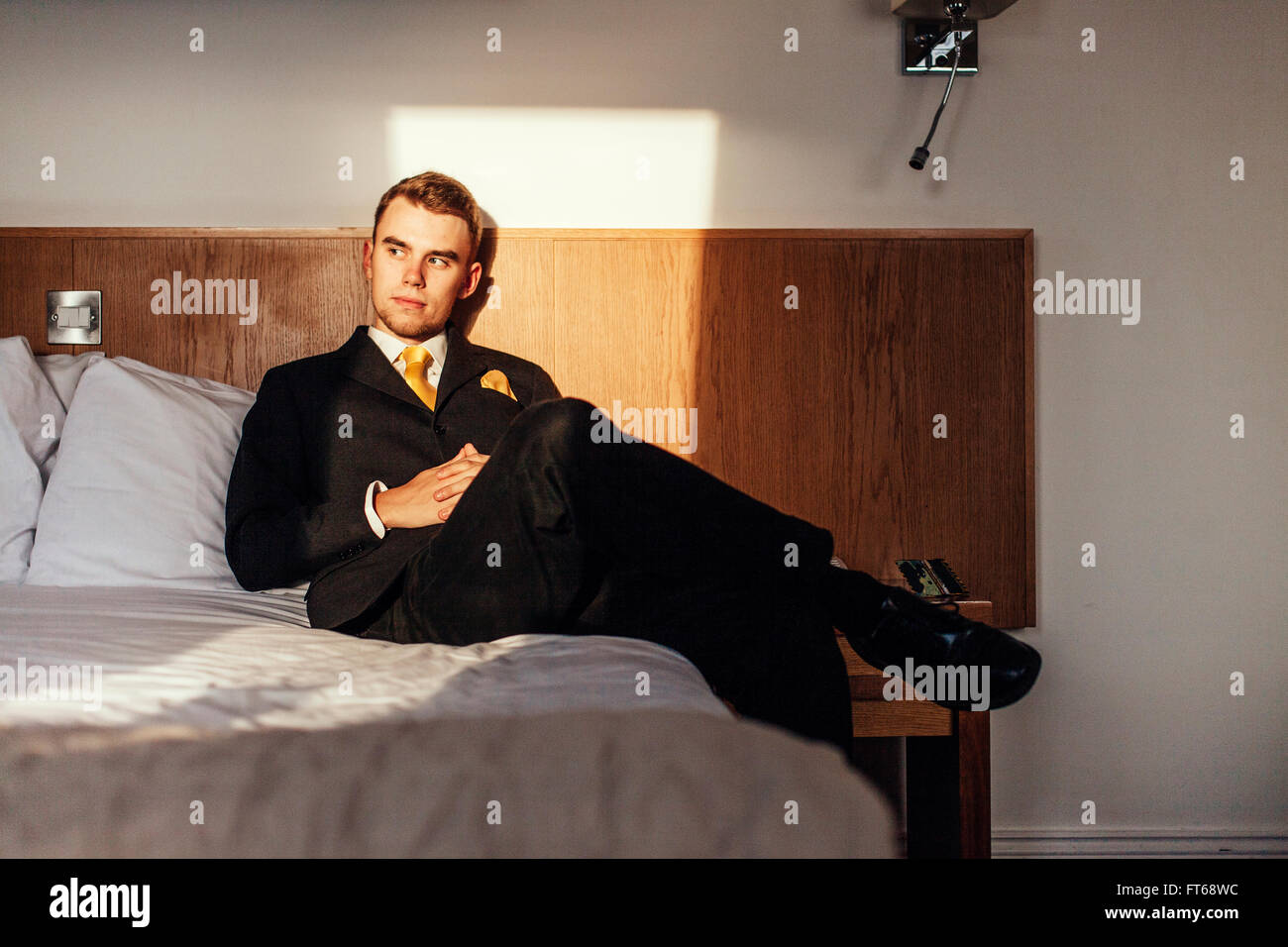 Thoughtful well-dressed businessmanman sitting on bed in hotel room - Stock Image