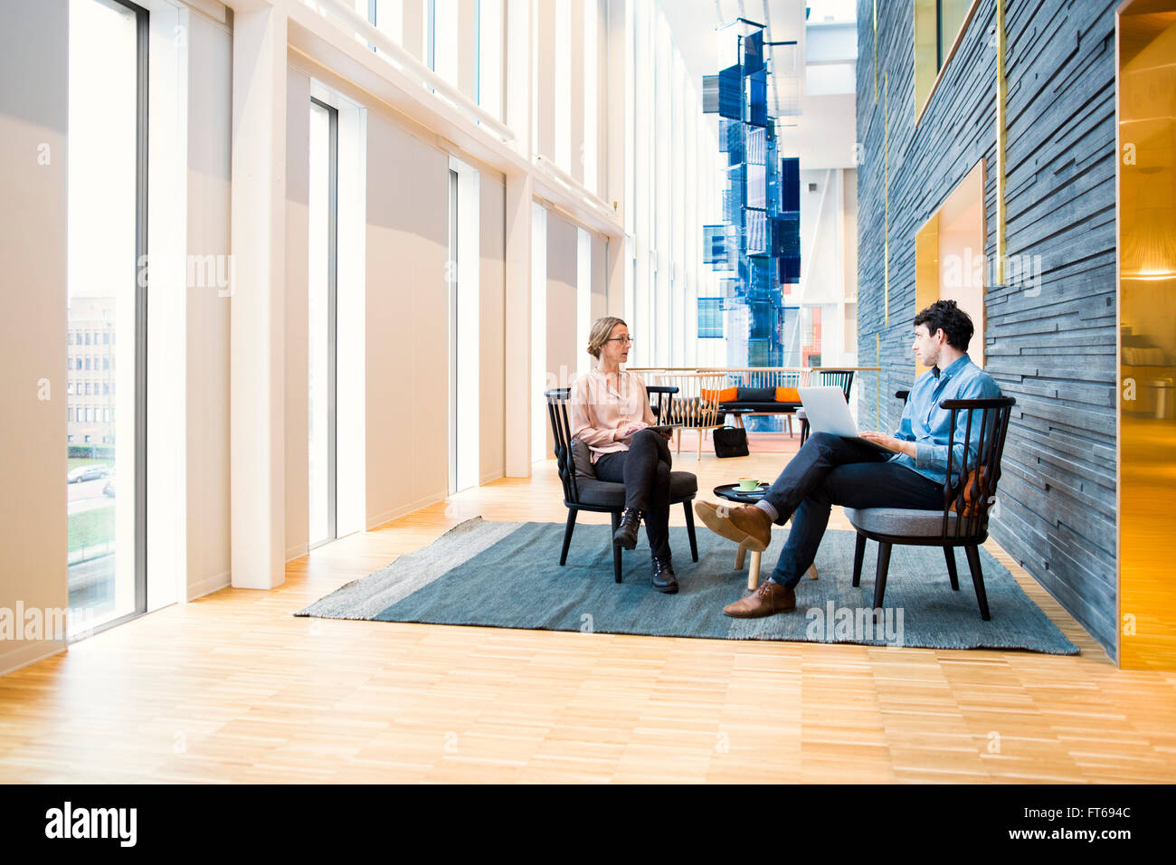 Full length of business people discussing in meeting at hotel lobby - Stock Image