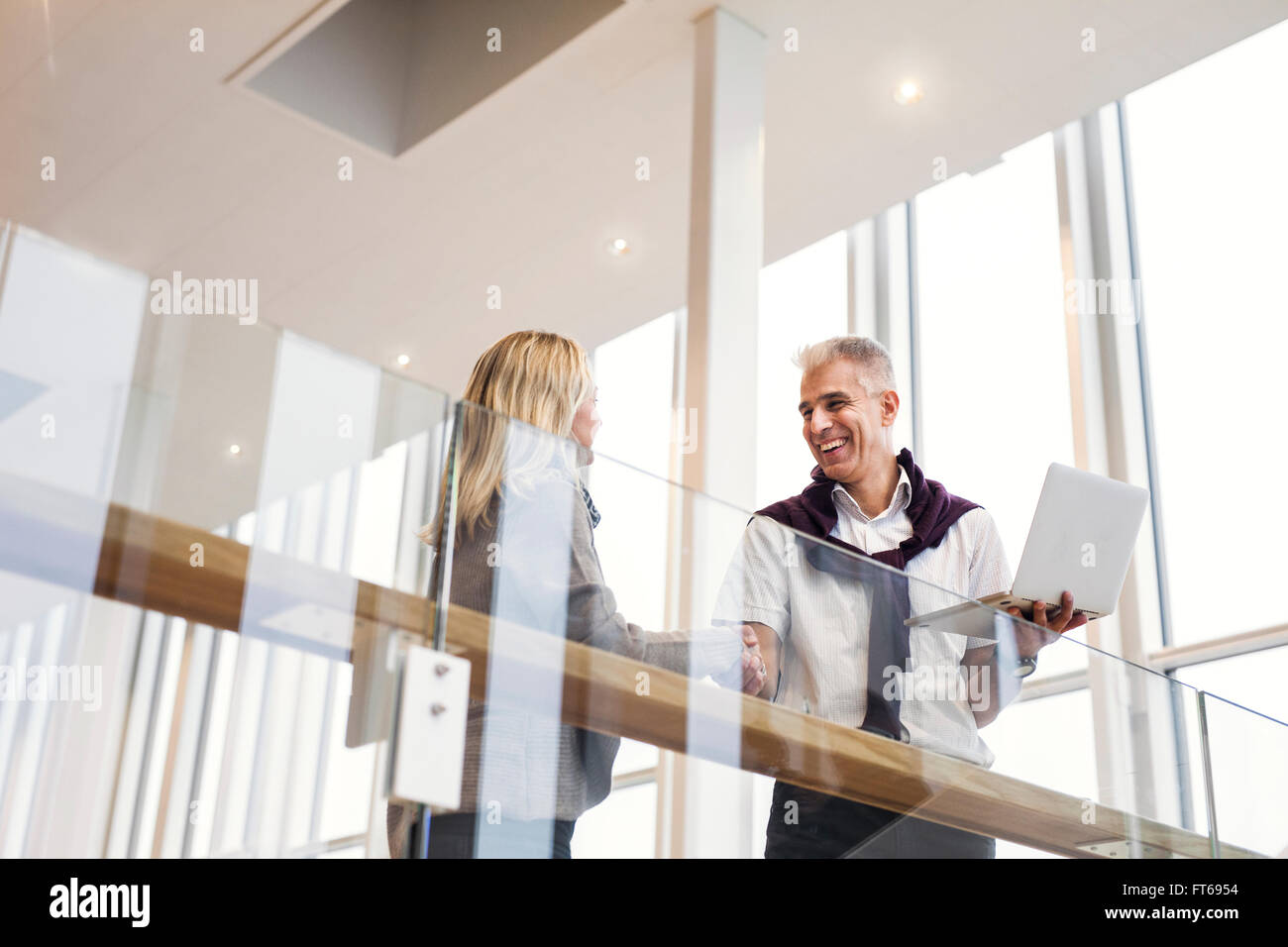 Low angle view of happy business people shaking hands at hotel lobby - Stock Image