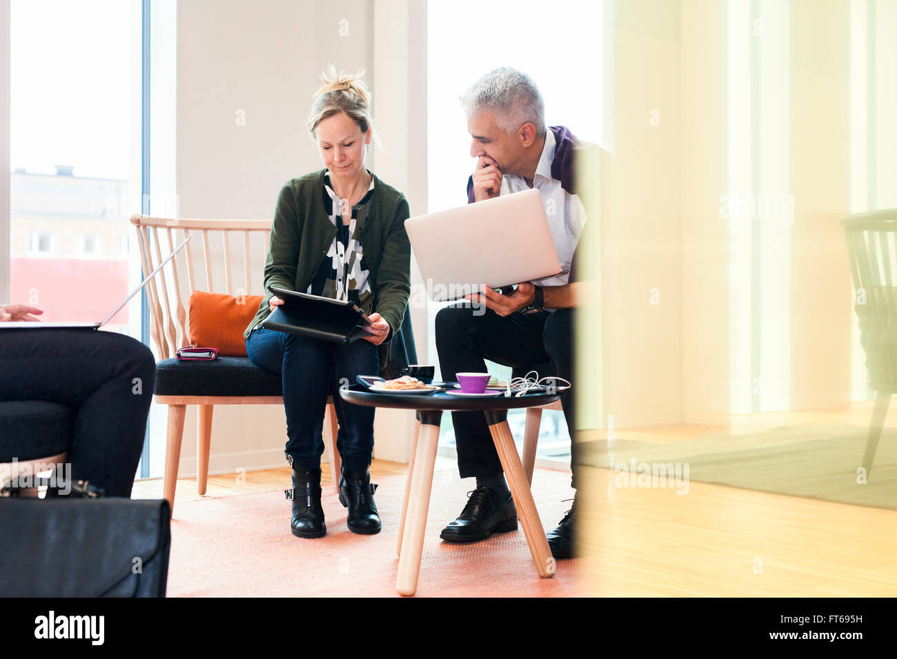 Business people using technologies at hotel lobby - Stock Image