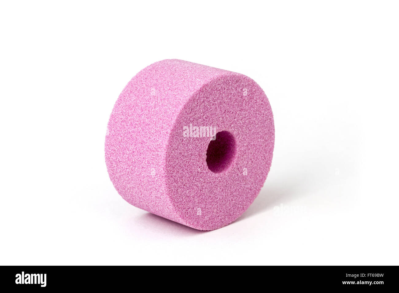 A pink abrasive wheel made out of corundum for grinding machine, photographed in the studio on a white background. - Stock Image