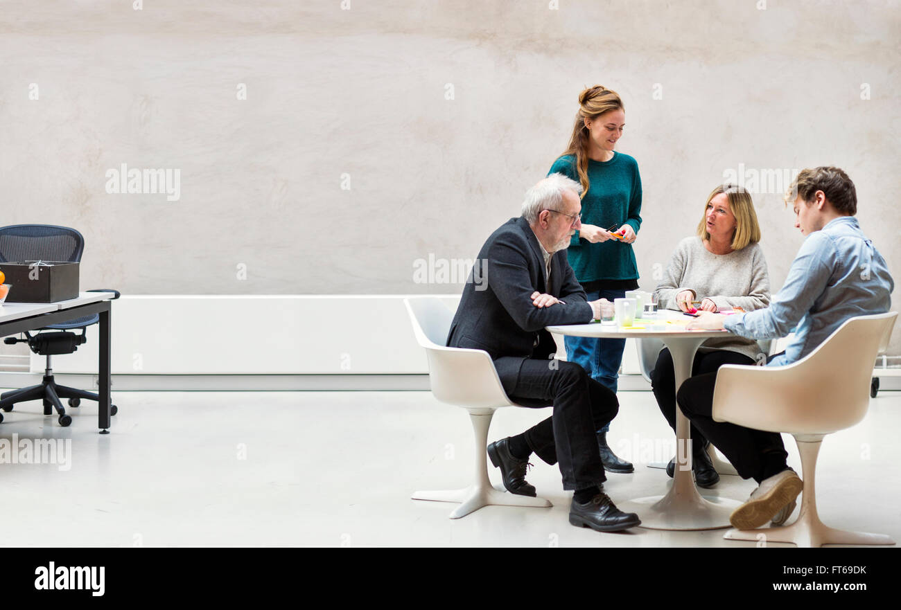 Team of business people having discussion at table in creative office - Stock Image