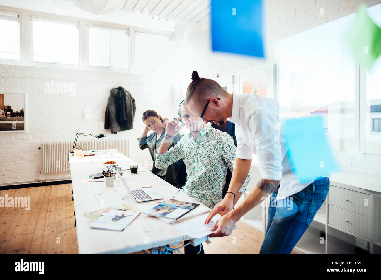 Team of business people working at table in creative office - Stock Image