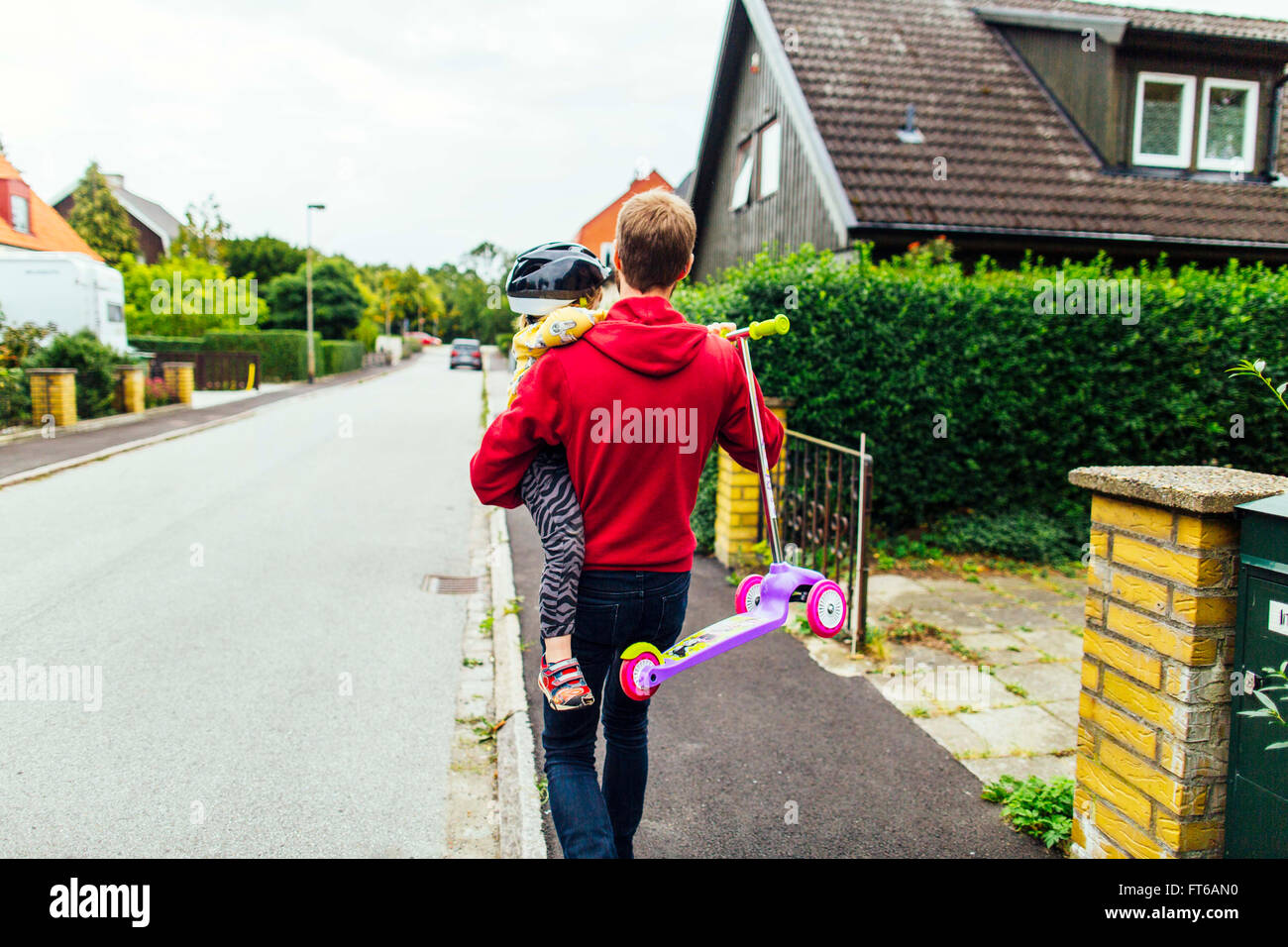 Rear view of man carrying daughter and push scooter on sidewalk - Stock Image