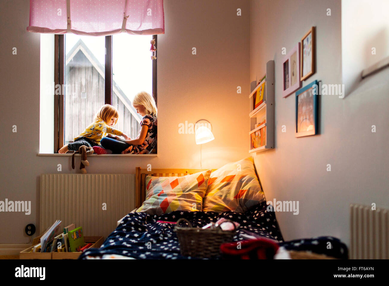 Sisters using digital tablet on window sill - Stock Image