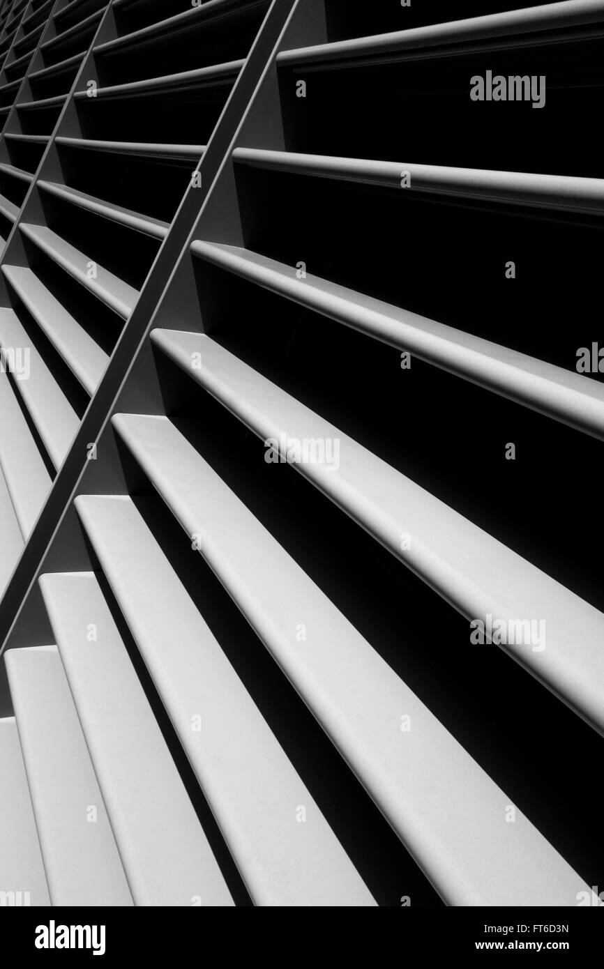 Modern architectural design of metal in the sunlight consisting of permanently mounted blades on a sloping facade - Stock Image