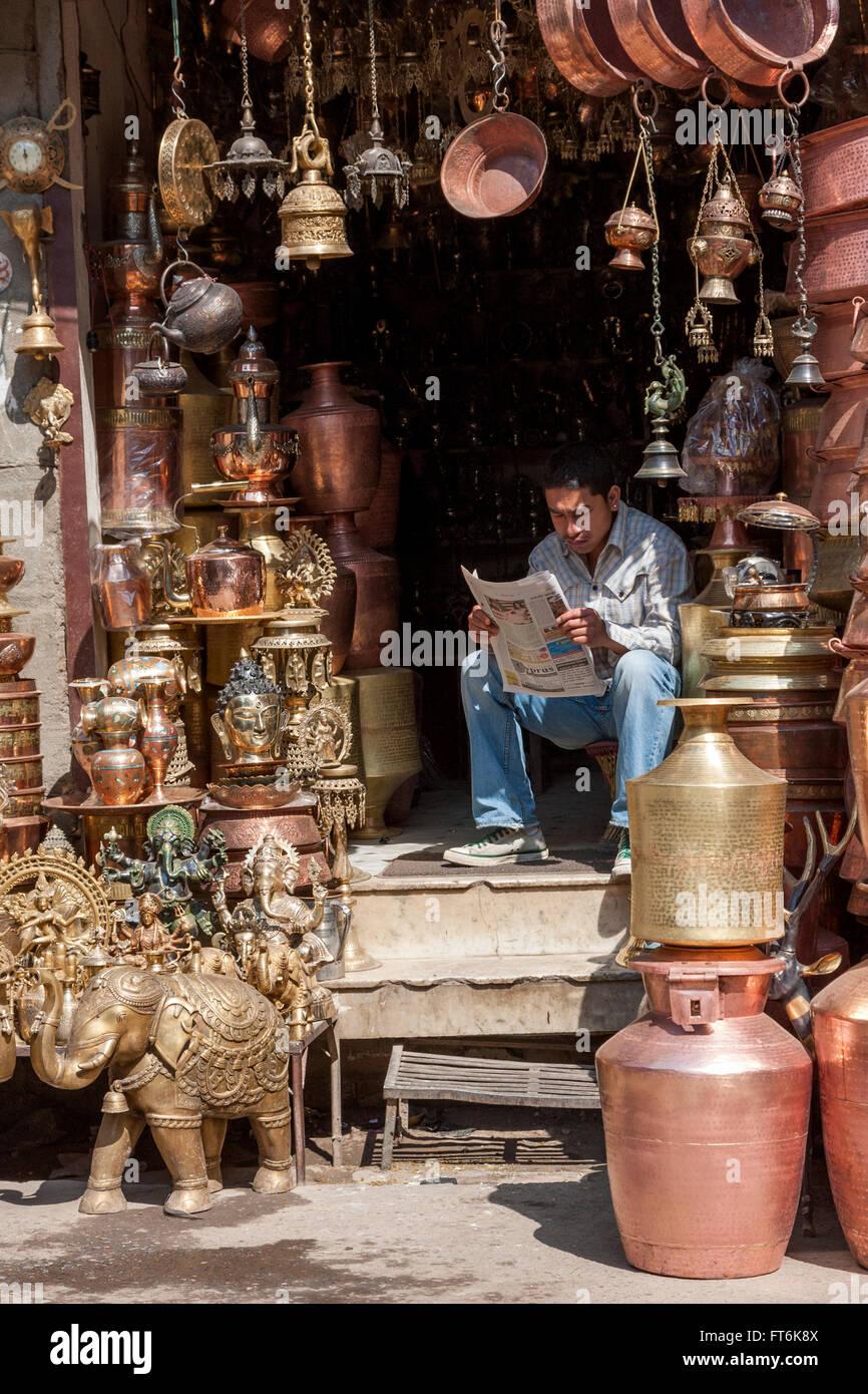 Nepal, Kathmandu.  Vendor of Brass Hindu and Buddhist Decorative Items and Utensils Reading the Newspaper. Stock Photo
