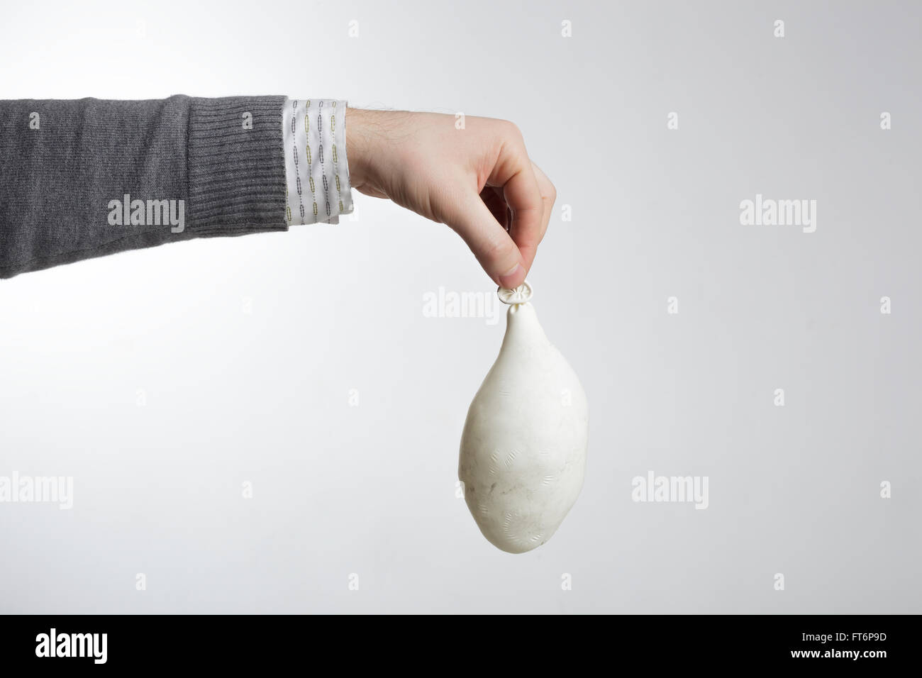 Man holding white balloon in hand - Stock Image