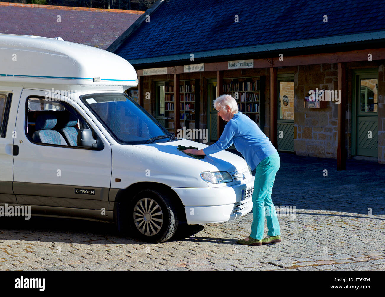 Senior woman washing her small motorhome, a Romahome Duo, UK - Stock Image