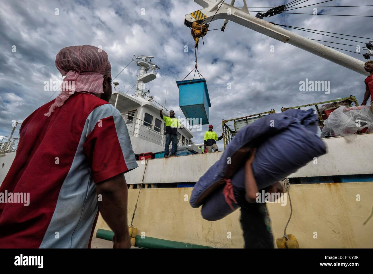 A dock worker unloads cargo from a ship at the port July 2, 2015 in Honiara, Solomon Islands. - Stock Image