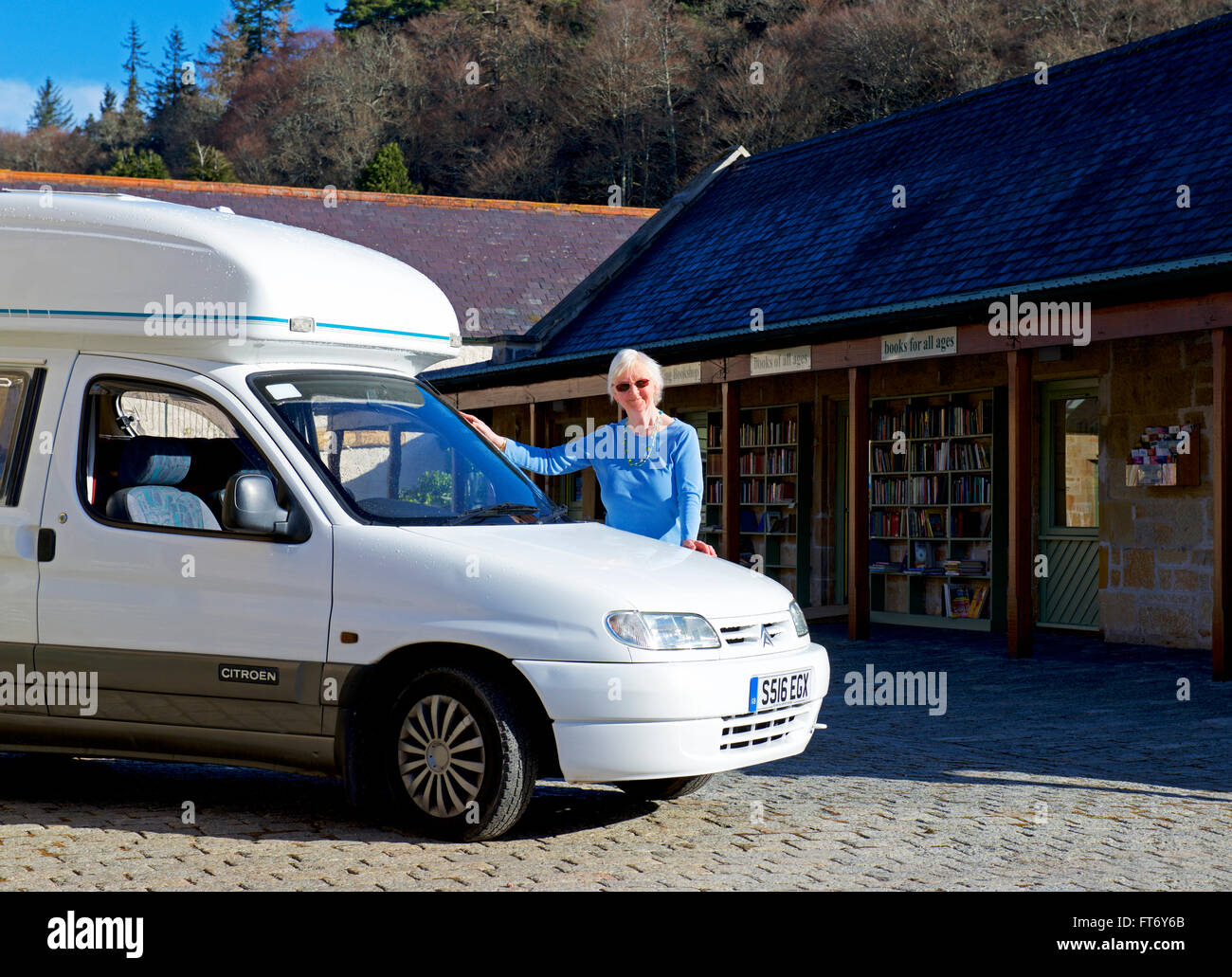 Senior woman standing next to her small motorhome, a Romahome Duo, UK - Stock Image