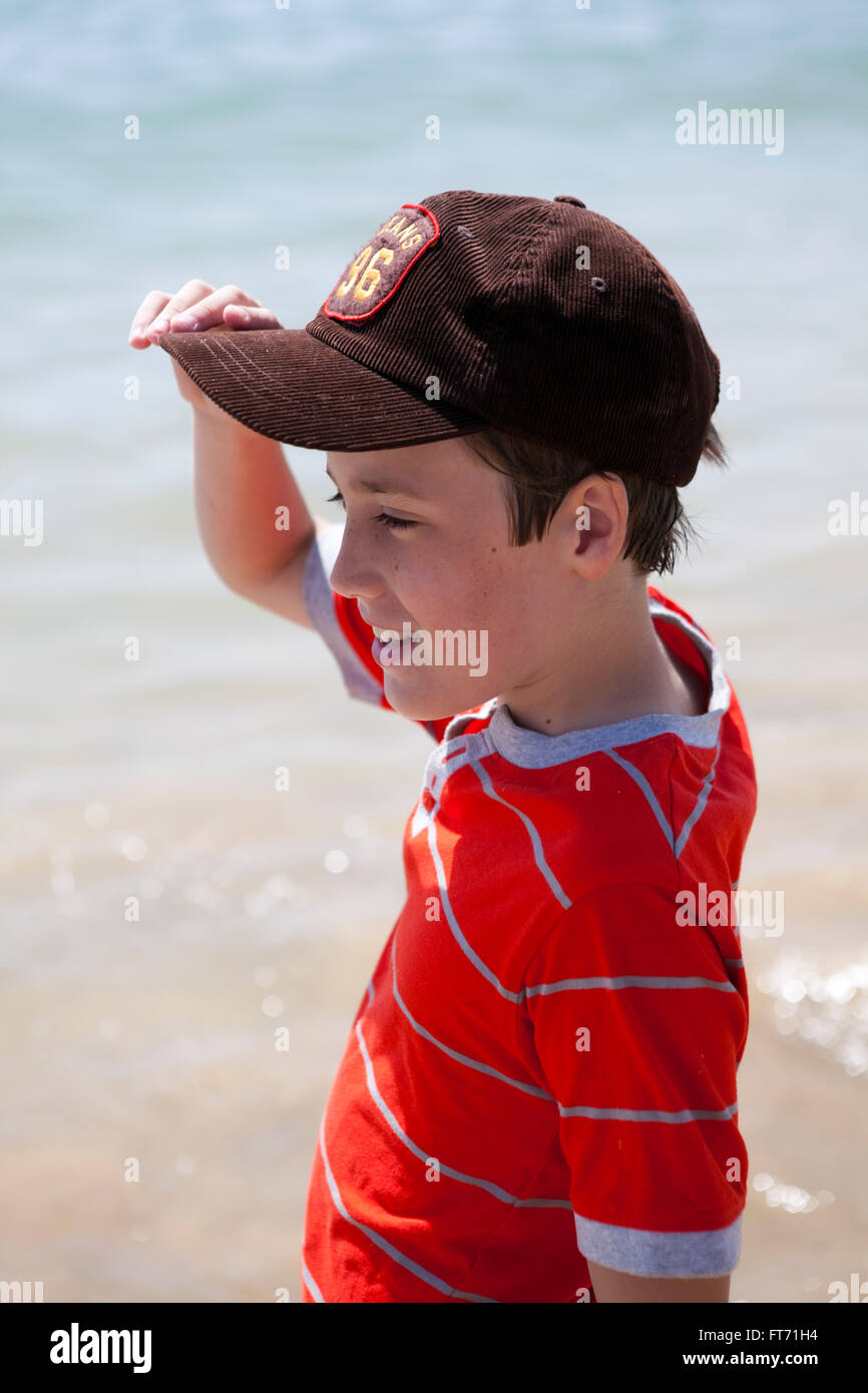 A small boy shelters his face from the midday sun on a beach in southern spain as he looks out to sea while on holiday. - Stock Image