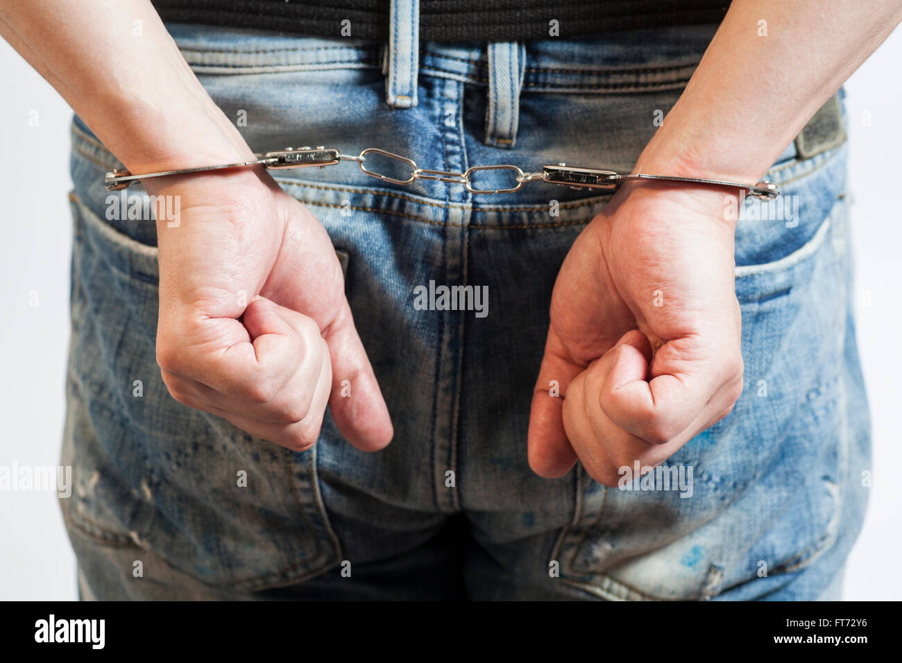 Close up of man in handcuffs arrested on white - Stock Image