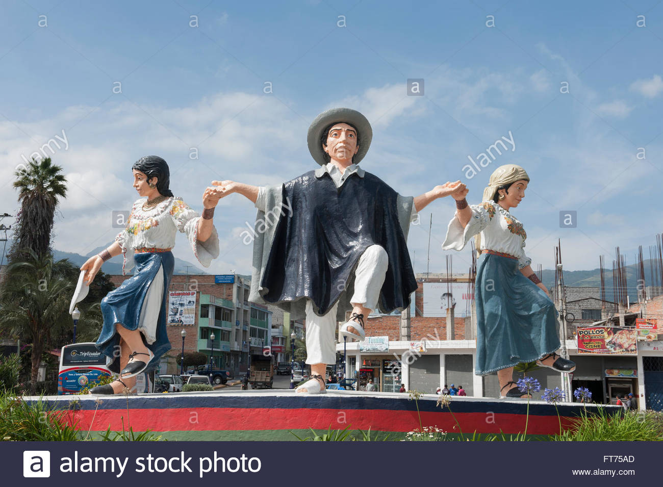 Otavalo Ecuador On a roundabout a statue of three indigenous people dancing and wearing typical clothing. - Stock Image