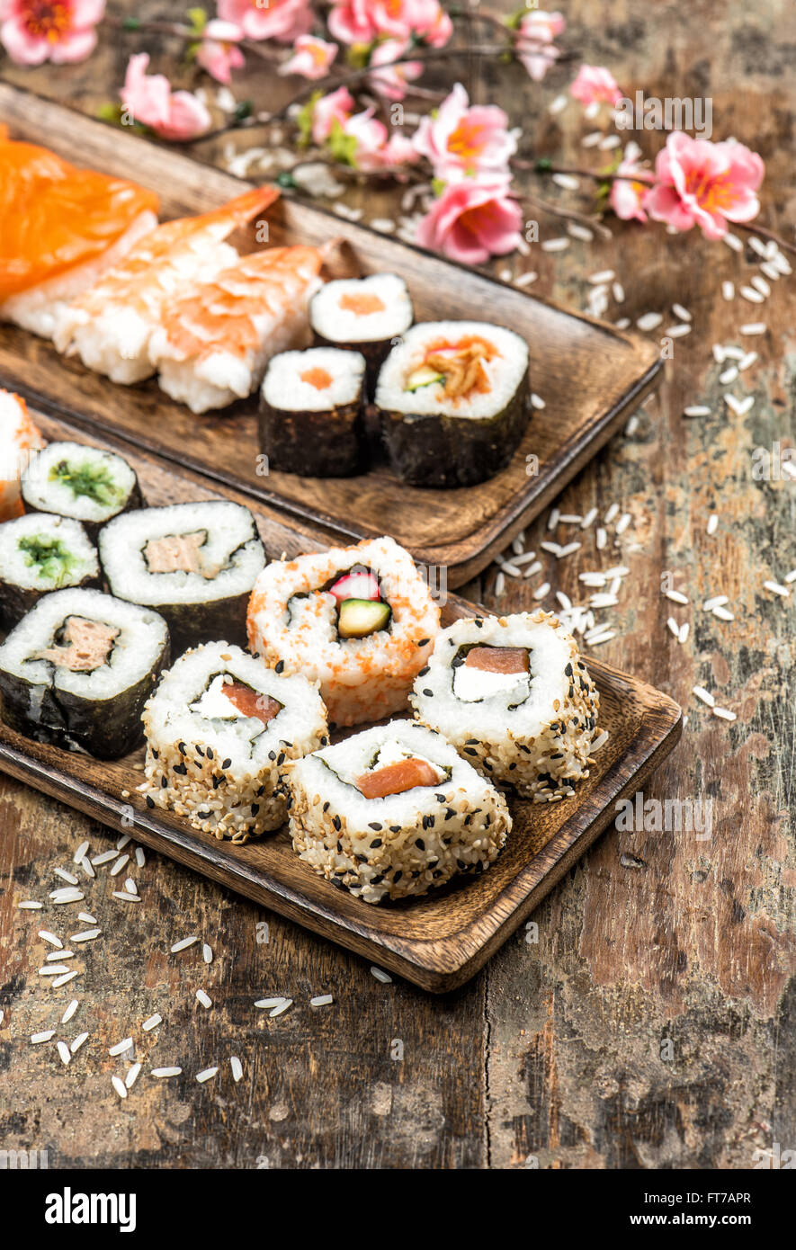 Sushi, maki, sashimi and sushi rolls on wooden background with spring flowers - Stock Image