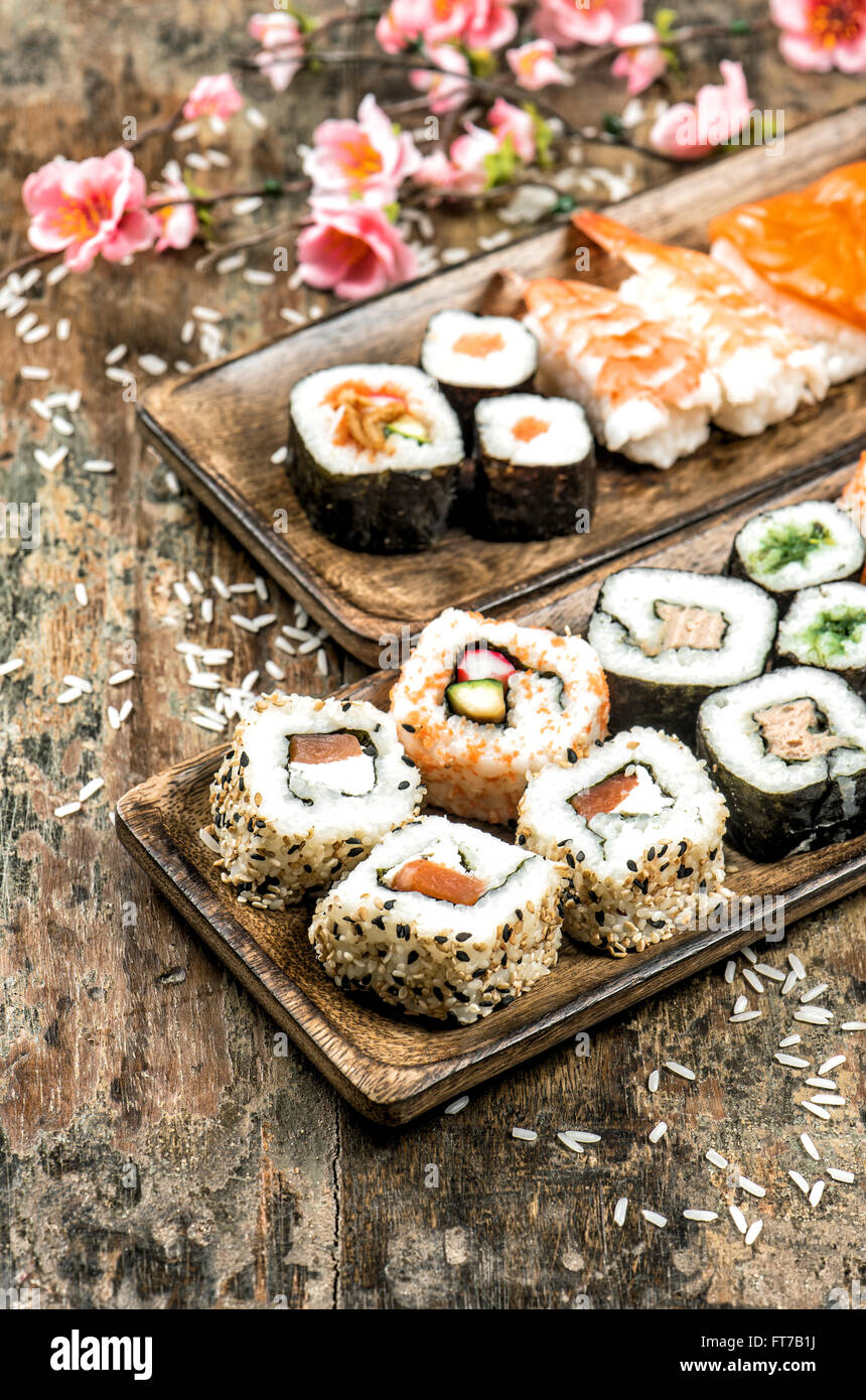 Sushi, maki, sashimi and sushi rolls on wooden background with spring flowers. Vintage style toned picture - Stock Image