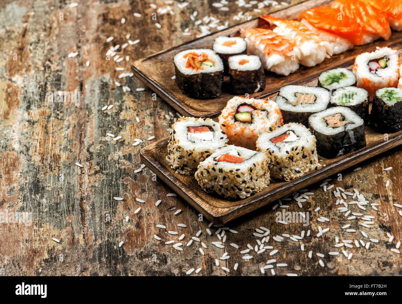 Sushi, maki, sashimi and sushi rolls on rustic wooden background - Stock Image