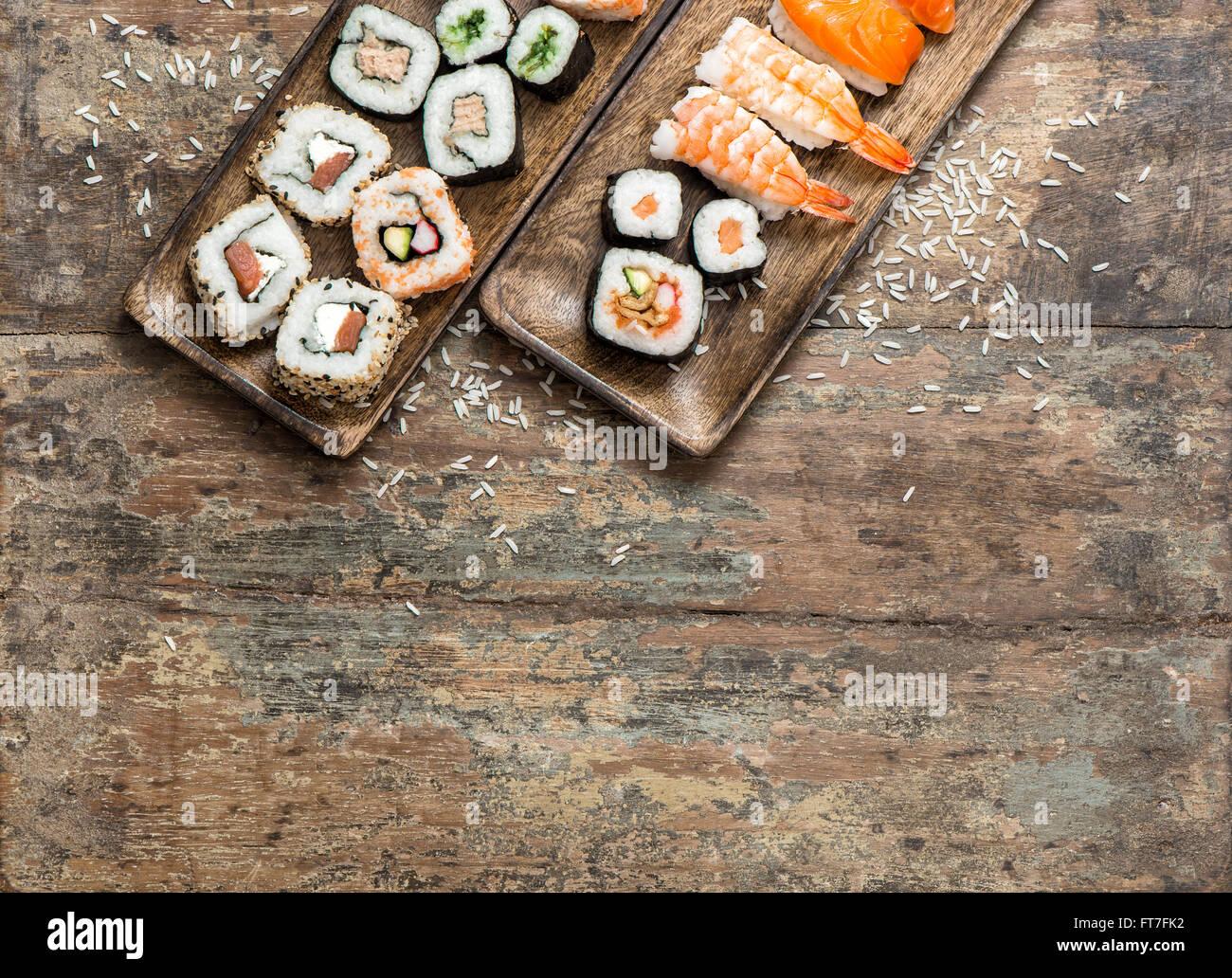 Traditional japanese food. Sushi rolls, maki, nigiri on wooden background - Stock Image