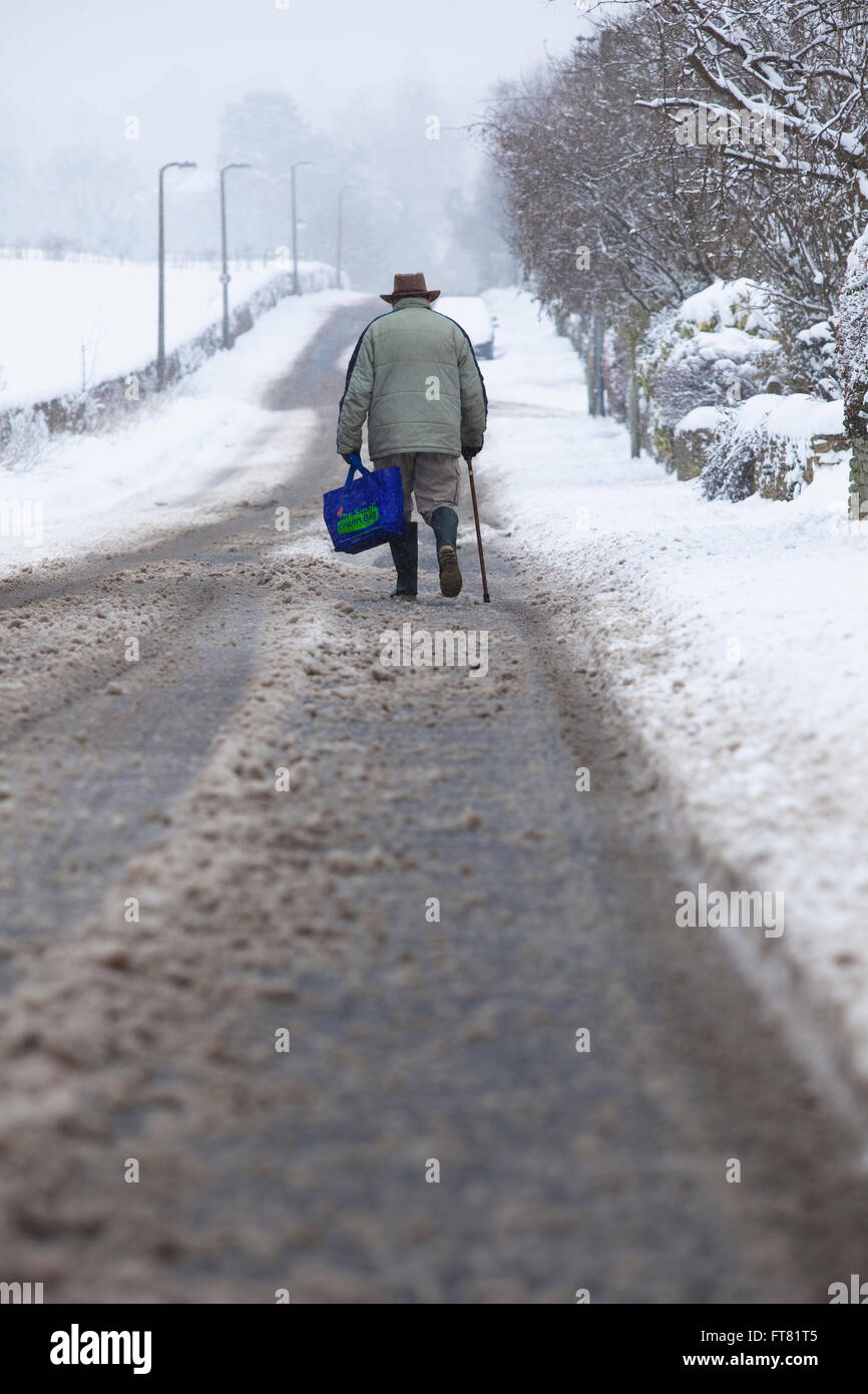 An old man possibly retired or a pensioner walks slowly in to town through snow covered streets in the depths of - Stock Image