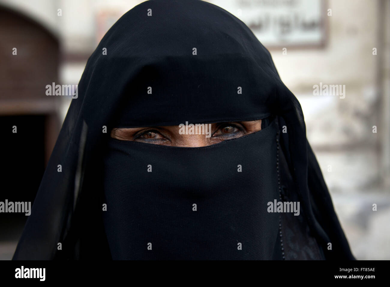 Saudi woman covered with black hijab and closeup of eyes - Stock Image