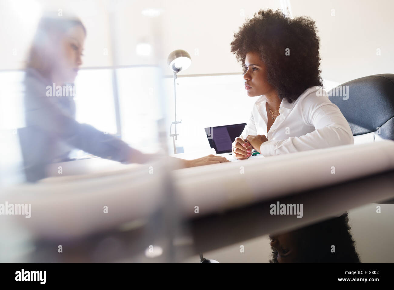 Team of two female architects, sitting at desk in office. The women talk reviewing a building plan. Medium shot - Stock Image