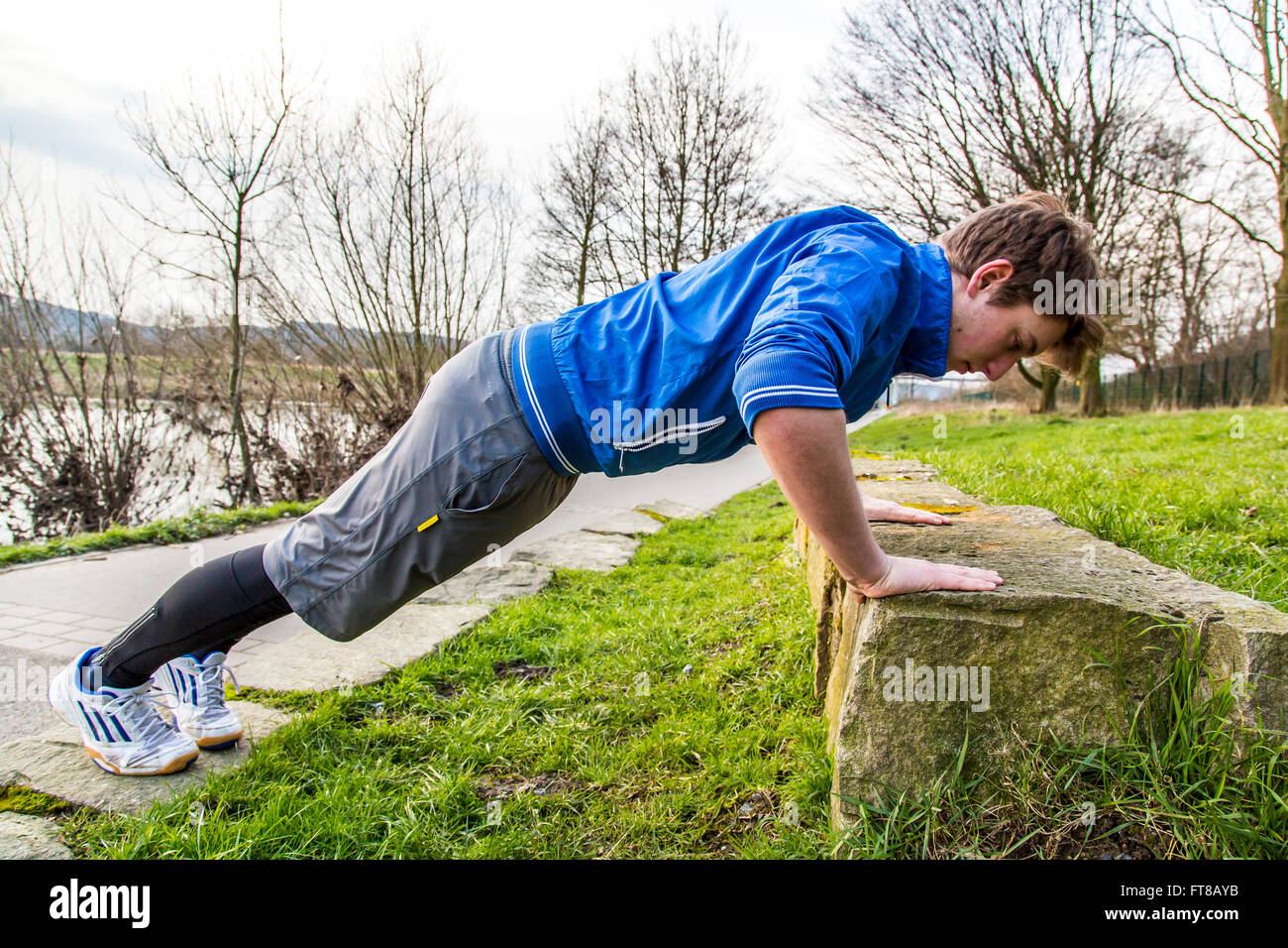 Young man is doing outdoor sports, fitness training, pushups, push ups, - Stock Image