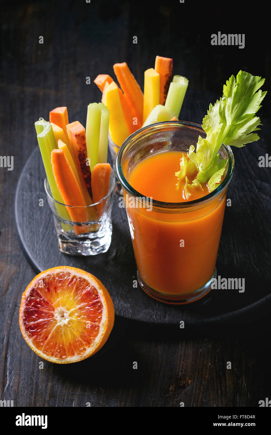 Sliced colorful raw carrots and celery as vegetarian snack, blood oranges with glass cup of fresh orange and carrot - Stock Image