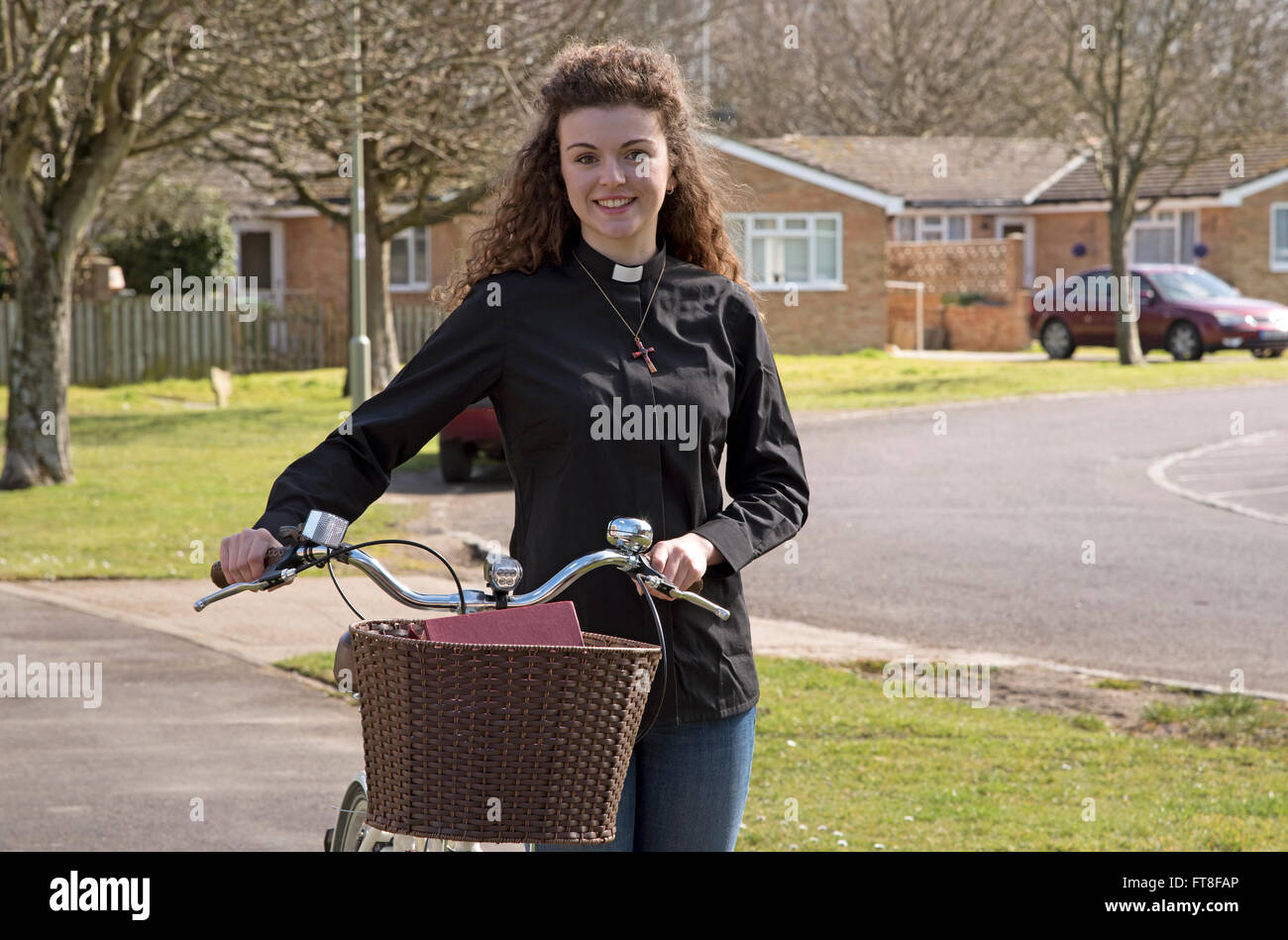 Young attractive parish priest using a bicycle as transport around her parish - Stock Image
