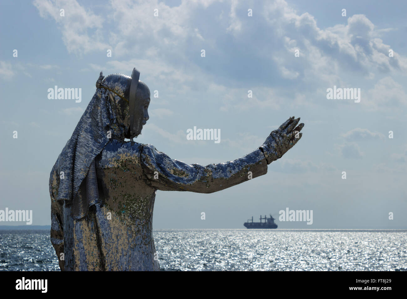 Close backlit view of a street mime artist wearing a sequin dress. Thessaloniki, waterfront, near White Tower against - Stock Image