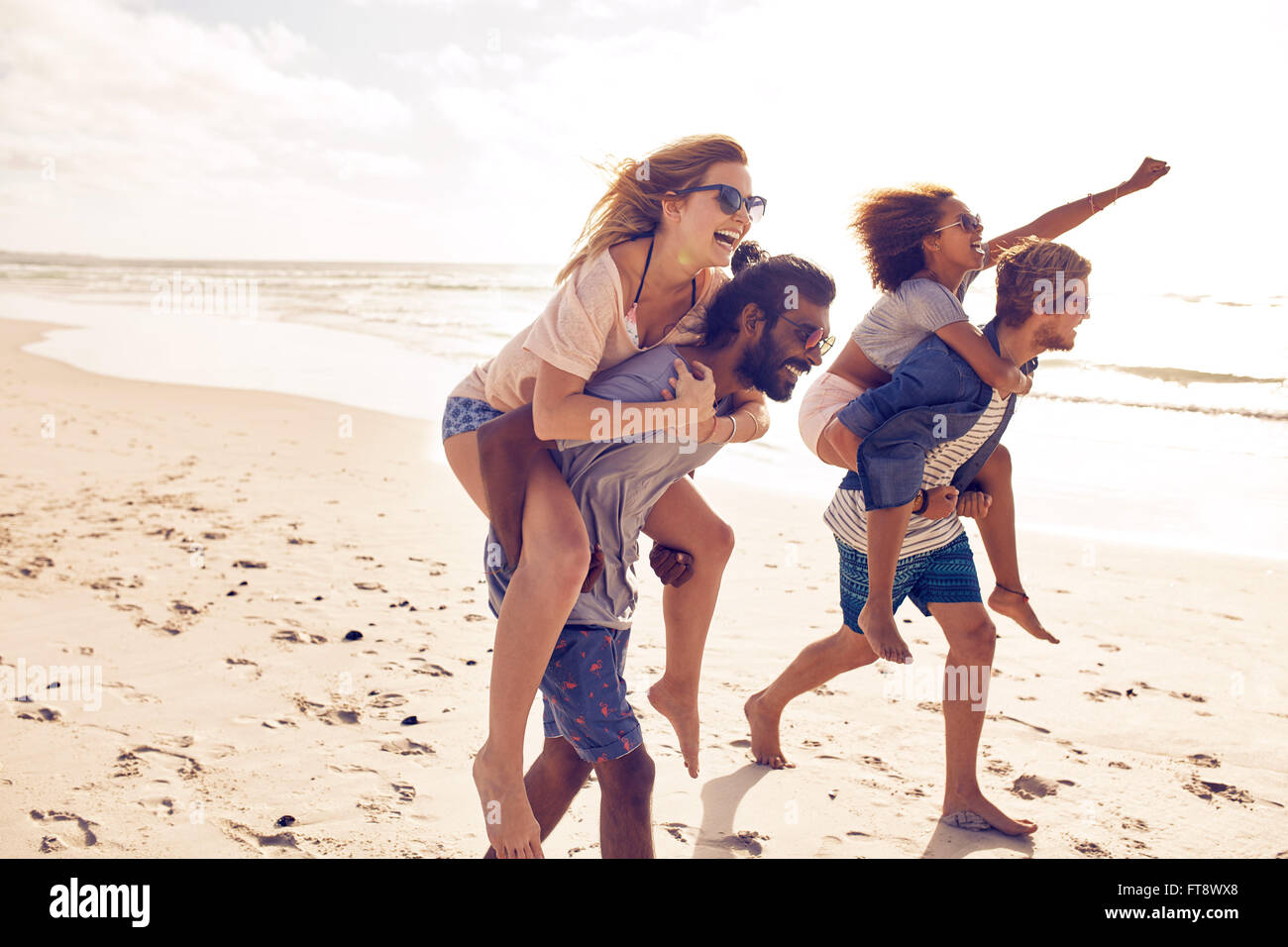 Two young men giving their girlfriends piggyback rides at the beach. Cheerful young friends enjoying summertime - Stock Image