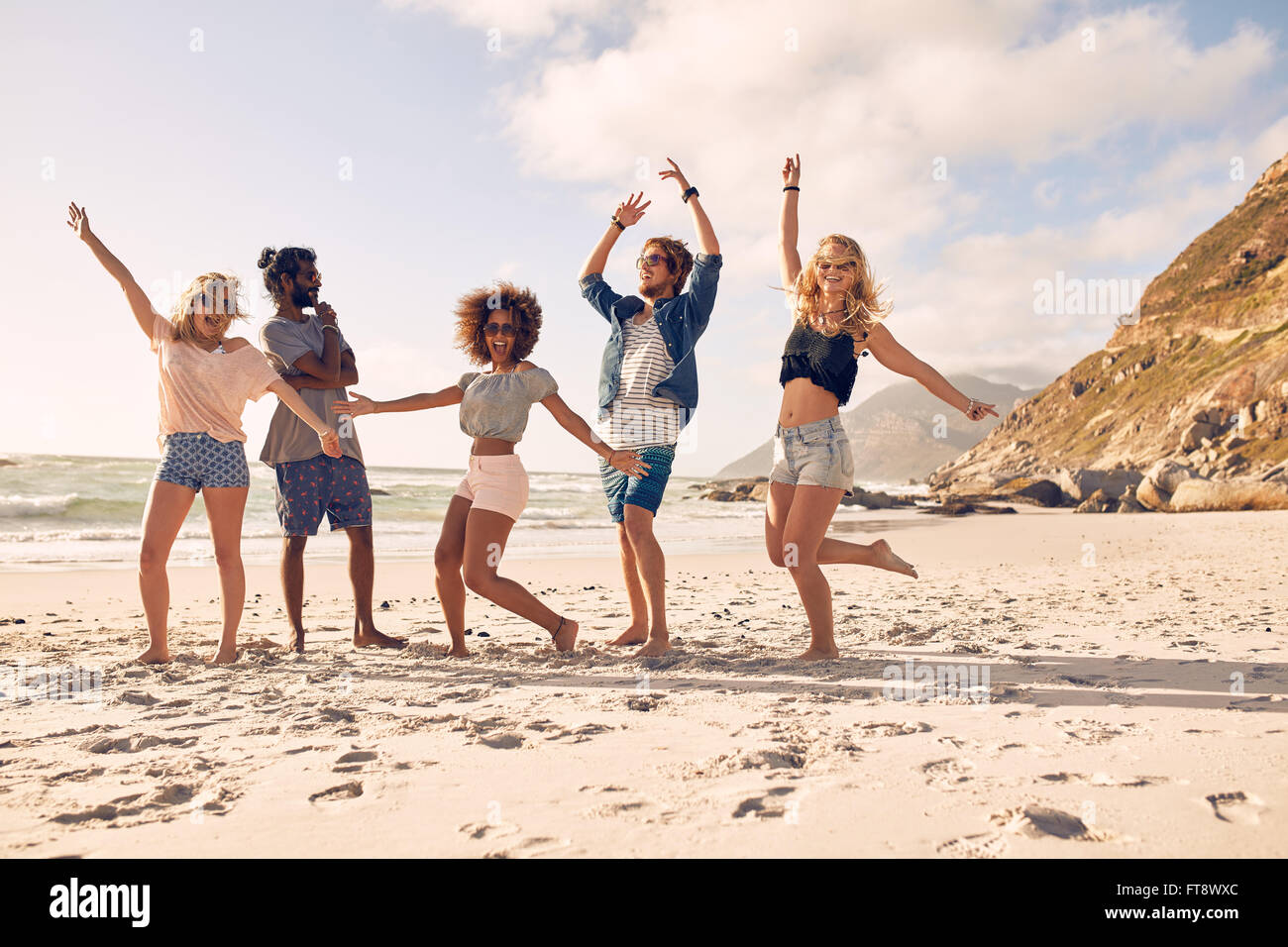 Multi-ethnic group of friends together on the beach having fun. Happy young people dancing on the beach. Group of - Stock Image
